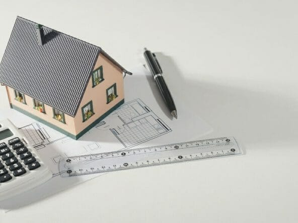 toy house with rule, pen, and a calculator